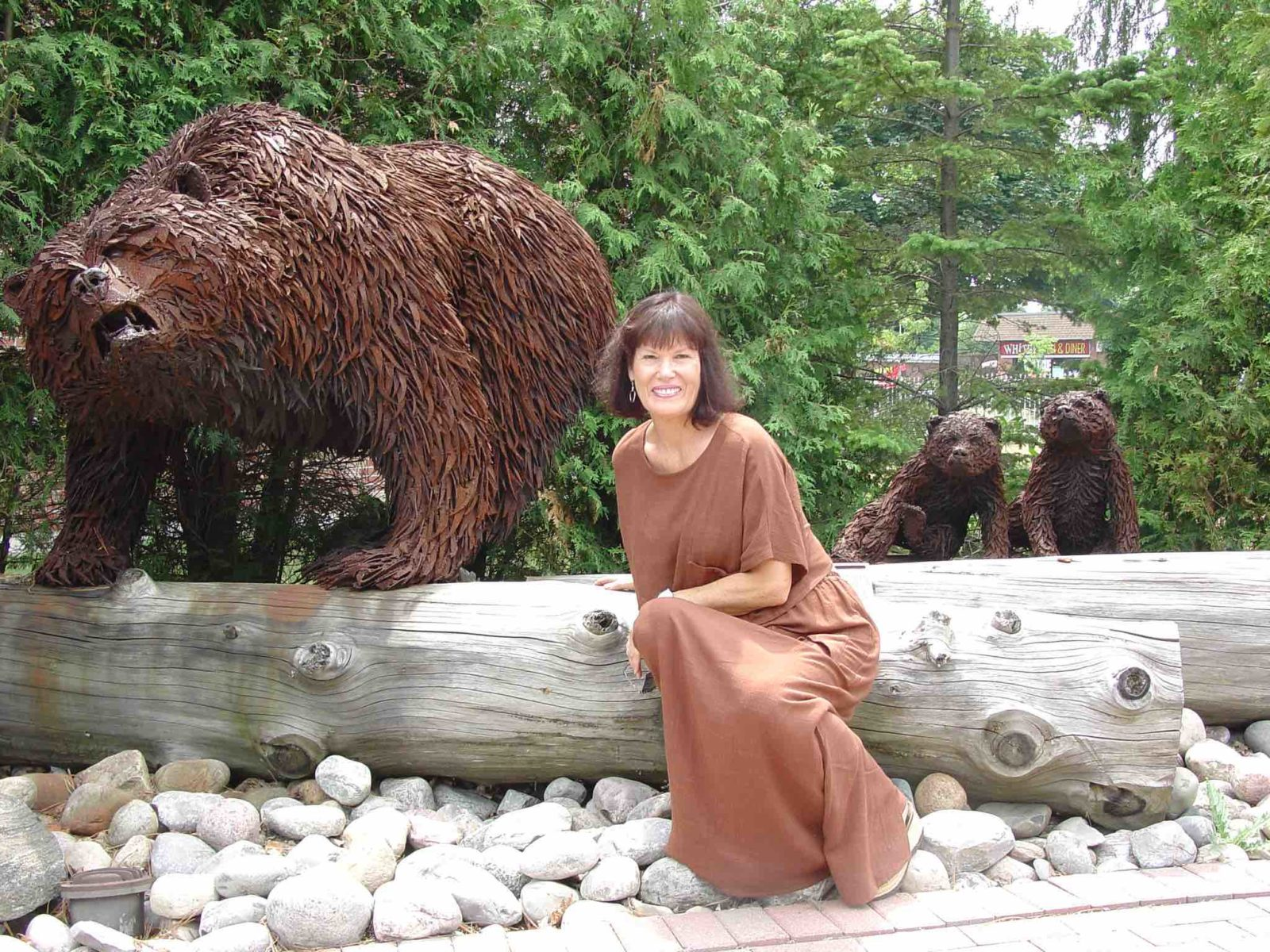 Artist Hilary Clarke Cole seated next to a metal statue of a growling bear