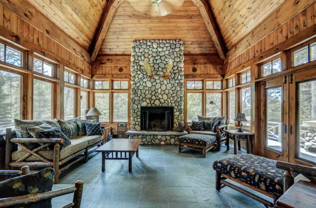 Luxury real estate on Bigwin island showing chic fireplace and Muskoka room