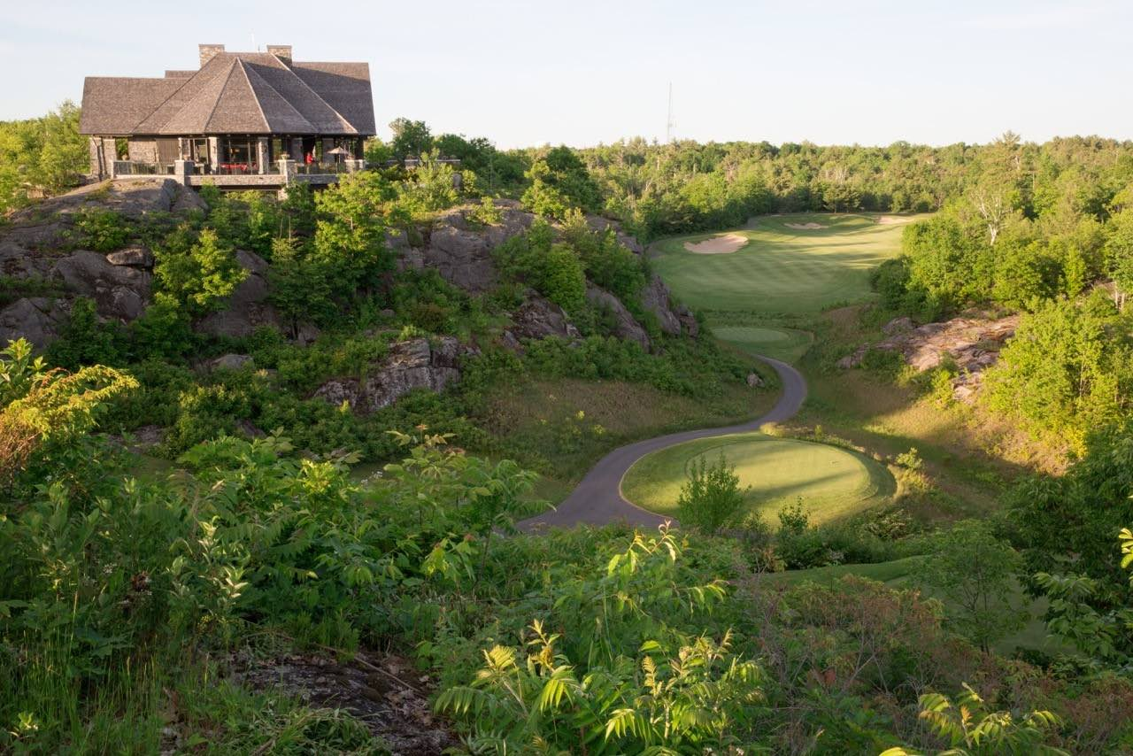 Muskoka Bay Golf Club with clubhouse overlooking tees is one of the top Muskoka golf courses