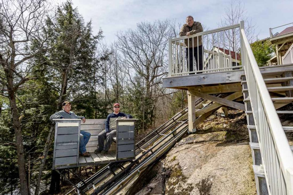 The Cottage LIfts elevation solutions team sitting on one of their Muskoka cottage lifts