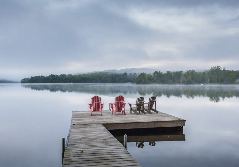 Dock and Muskoka chiars in Lake of Bays with morning mist over lake